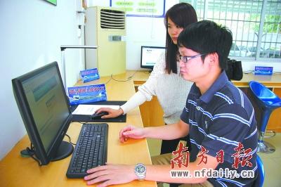新兴县行政服务中心内,工作人员向市民演示网上办事大厅的操作