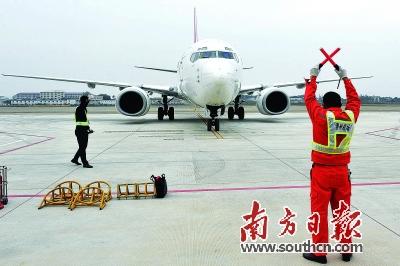 机场工作人员引导飞机驶进停机位
