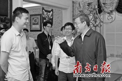 林氏木业创始人林佐义(左)向佛山市长鲁毅(右)介绍林氏木业的发展