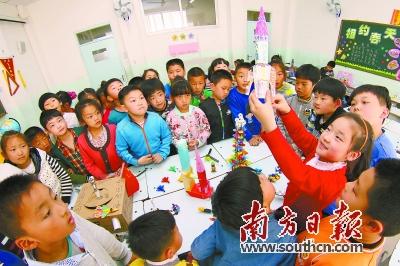 """22日,山东某学校学生向同学们介绍自己用纸盒制作的""""火箭""""."""